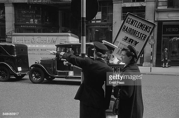 A police officer helping a woman with directions on Piccadilly Mayfair London circa 1953