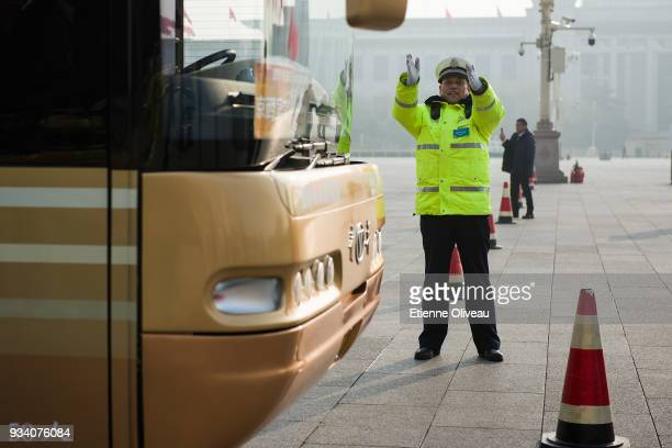 Police Officer helps a cauch driver to park on Tiananmen Square before the seventh plenary session of the 13th National People's Congress at the...