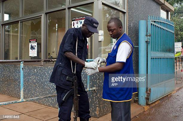 A police officer helps a worker to put on his gloves to protect himself from virus infection on July 31 2012 at the Mulago Hospital in Kampala where...