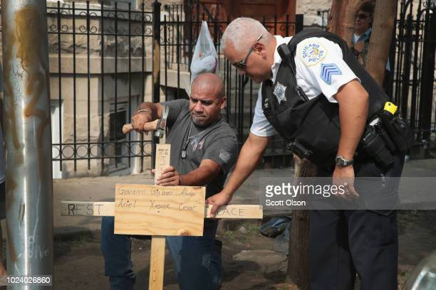 A police officer helps as Omar Acevedo pounds a cross bearing the names of victims into the dirt outside a home where eight people perished including...