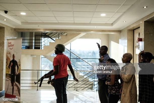 A police officer helps people to escape the building after a bomb blast from the office block attached to DusitD2 hotel in Nairobi Kenya on January...