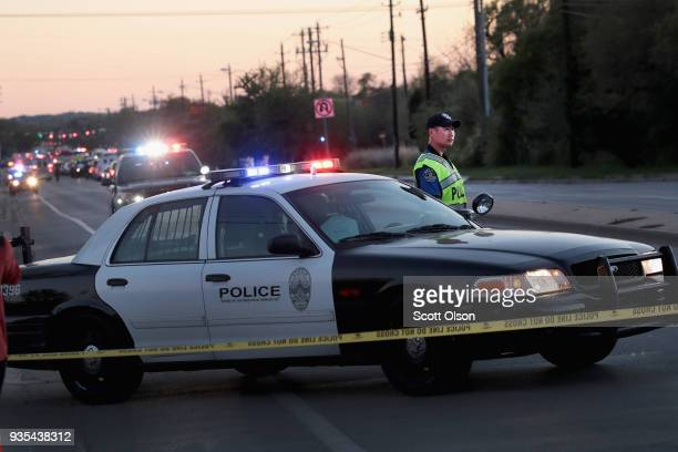 A police officer helps to secure the area after one person was injured by a package containing an incendiary device at a nearby Goodwill store on...