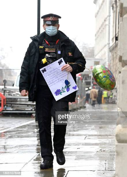 Police officer holding a letter and balloon from a well-wisher walks into St Bartholomew's Hospital where Prince Philip, Duke of Edinburgh is being...