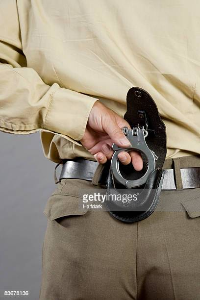 A police officer holding handcuffs