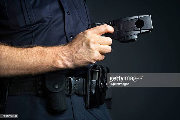 police officer holding stun gun - police taser stock pictures, royalty-free photos & images