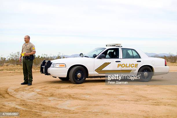 police officer holding stungun - police taser stock pictures, royalty-free photos & images