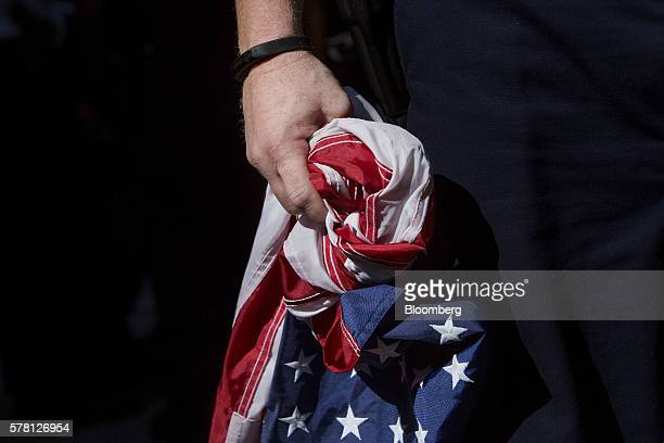 A police officer holds a confiscated American flag after arresting a protester during demonstration at the Republican National Convention in...
