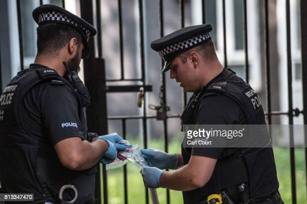 A police officer holds a knife in an evidence bag after removing it from the scene of an arrest near Elephant and Castle Station during Operation...