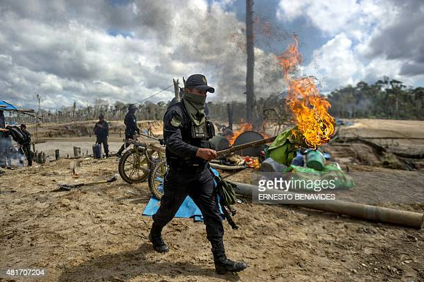A police officer holds a lit torch during an interdiction operation in the illegal gold mining area of La Pampa in Madre de Dios southern Peruvian...