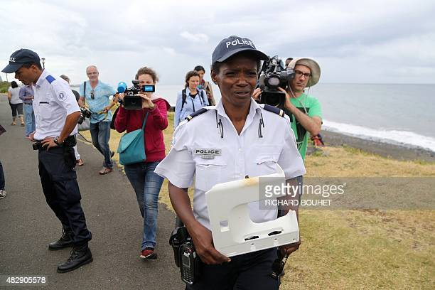 A police officer holds a piece of plastic found on the sea front of SaintDenis on the French Indian Ocean island of La Reunion on August 4 2015 Last...