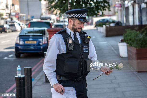 A police officer holds a rose given to him by a wellwisher to place near the scene of a terror attack in Finsbury Park in the early hours of this...