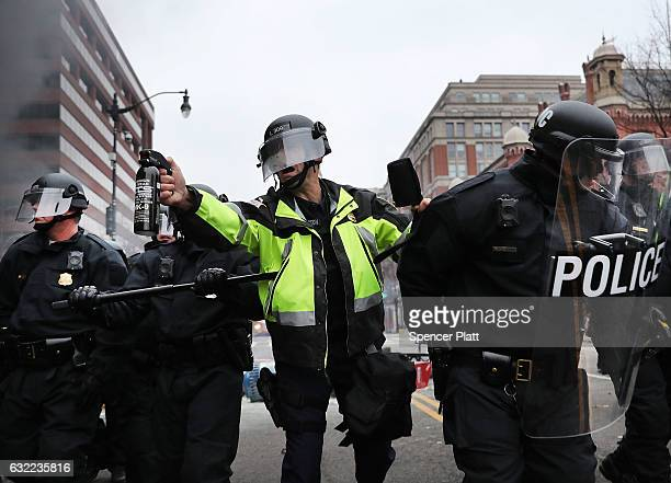 Police officer holds a tear gas cannister as police and demonstrators clash in downtown Washington after a limo was set on fire following the...
