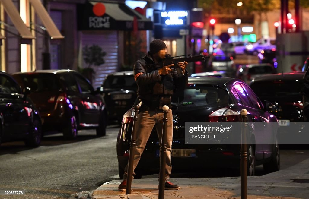 TOPSHOT - A police officer holds an assault rifle near the site of a shooting at the Champs Elysees in Paris on April 20, 2017. French anti-terror prosecutors said they opened a probe today into the shooting on Paris's Champs Elysees that killed one police officer and wounded two others. France's interior ministry said the attacker was killed after opening fire on police in the early evening on the world-famous boulevard. FIFE