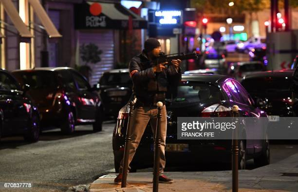 TOPSHOT A police officer holds an assault rifle near the site of a shooting at the Champs Elysees in Paris on April 20 2017 French antiterror...