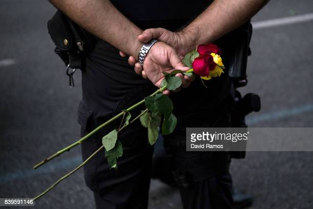 A police officer holds roses during a demonstration against the last week's terrorist attacks on August 26 2017 in Barcelona Spain Hundreds of...