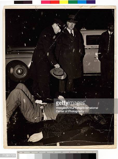 A police officer holds the hat of a man who lies dead on the street after being hit by a car on a snowy day New York New York circa 1942 Photo by...