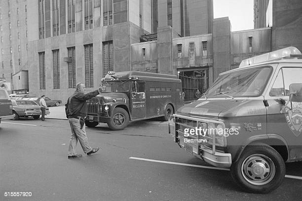 A police officer holds traffic outside the Manhattan District Court as a police van carrying Mark Chapman 12/11 returns him to Bellevue Hospital...