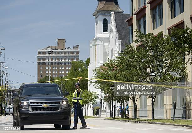 A police officer holds up a tape in front of the Emanuel AME Church June 18 2015 in Charleston South Carolina after a mass shooting at the church on...