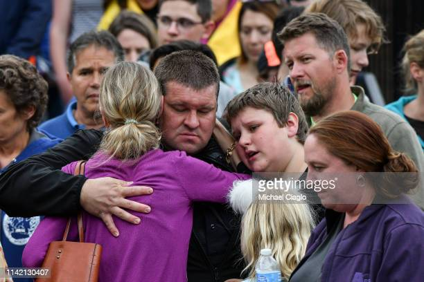 A police officer hugs his family after they were evacuated to the Recreation Center at Northridge after at least seven students were injured during a...