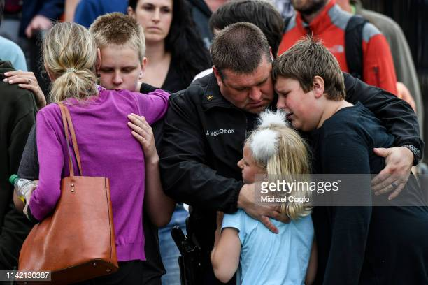 A police officer hugs his kids after they were evacuated to the Recreation Center at Northridge after at least seven students were injured during a...