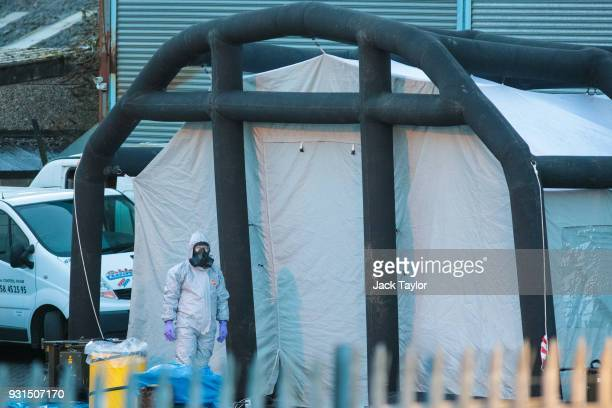 A police officer in a forensics suit and protective mask stands by a forensics tent outside a vehicle recovery centre as investigations continue into...