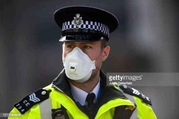 Police officer in a mask stands guard outside St Thomas' Hospital on April 09, 2020 in London, England. Prime Minister Boris Johnson is still being...