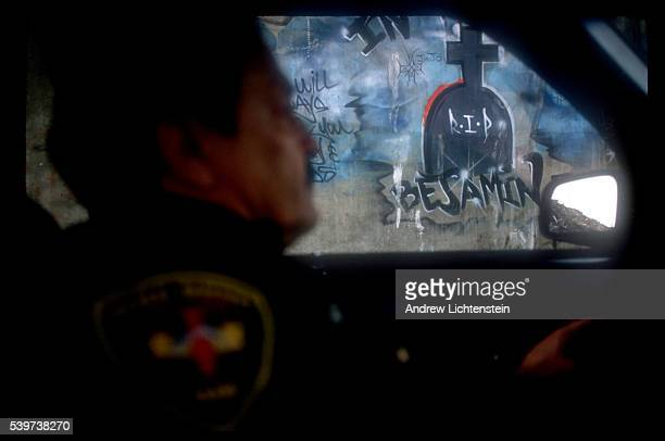 Police officer in Bridgeport, Connecticut's Tactical Narcotics Team cruises past one of many grafitti murals for a victim of street violence. In the...