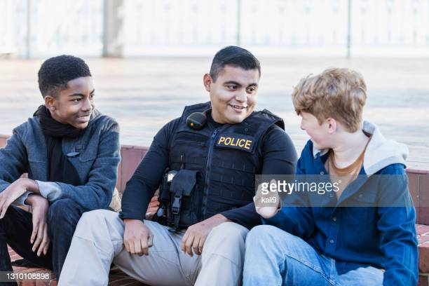 police officer in community, sitting with two youths - police force stock pictures, royalty-free photos & images
