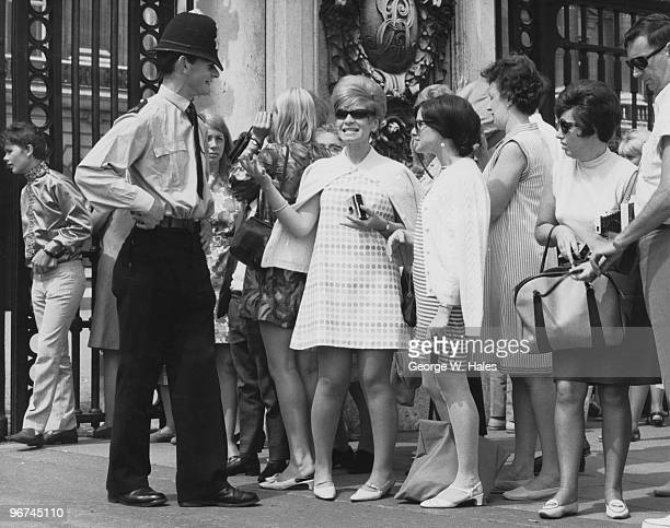 A police officer in conversation with tourists at the gates of Buckingham Palace London 12th July 1967