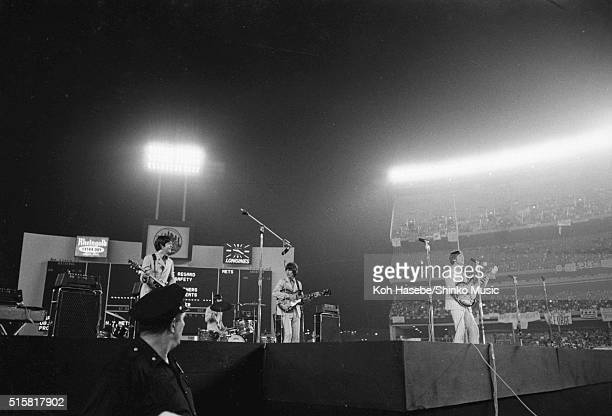 A police officer in front of the stage turns to watch as the The Beatles perform at Shea Stadium New York August 23 1966 LR Paul McCartney Ringo...