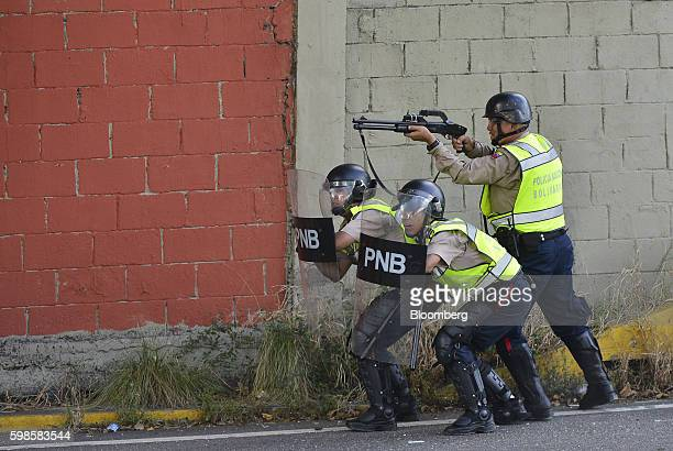 A Police officer in riot gear fires a weapon during a protest in Caracas Venezuela on Thursday Sept 1 2016 Hundreds of thousands of Venezuelans...