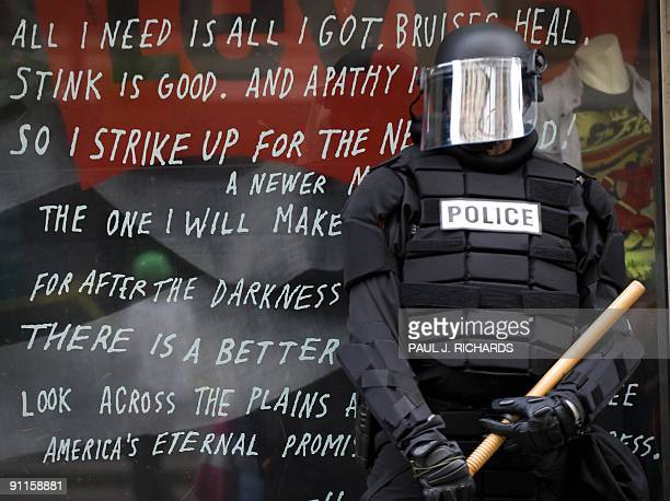 A Police officer in riot gear protects a store front as protesters take to the streets of downtown Pittsburgh Pennsylvania just a few blocks from the...