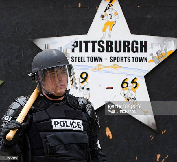 A police officer in riot gear protects a store front as protestors take to the streets of downtown Pittsburgh Pennsylvania just a few blocks from the...
