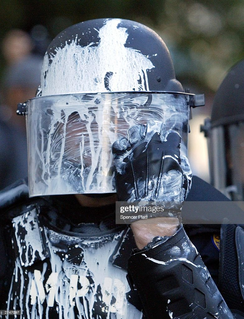 A police officer in riot gear wipes off a substance that was thrown during clashes with anti globalization protesters November 20, 2003 on the fourth day of the summit to create a Free Trade Area of the Americas (FTAA) being held in Miami, Florida. Hundreds of protesters, including groups of anarchists, clashed with the police throughout the morning as the protesters unsuccessfully tried to make their way to the summit building. Much of the city of Miami is in a police lockdown, with thousands of businesses closed and a steel barricade circling the summit area.