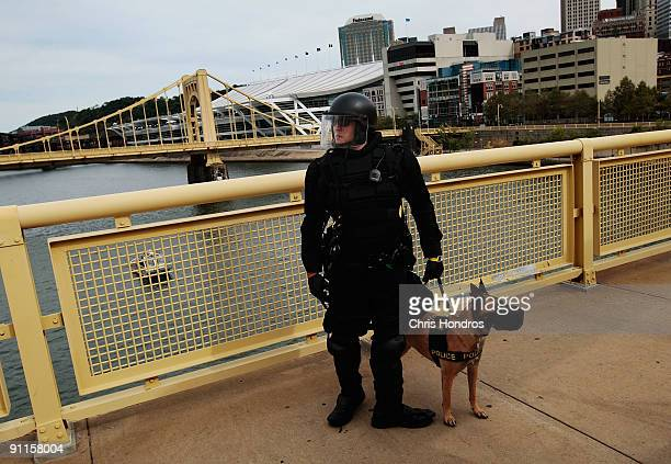 A police officer in riot gear with a police dog stands on the 7th Street Bridge near the convention center where the G20 Summit meeting is being held...