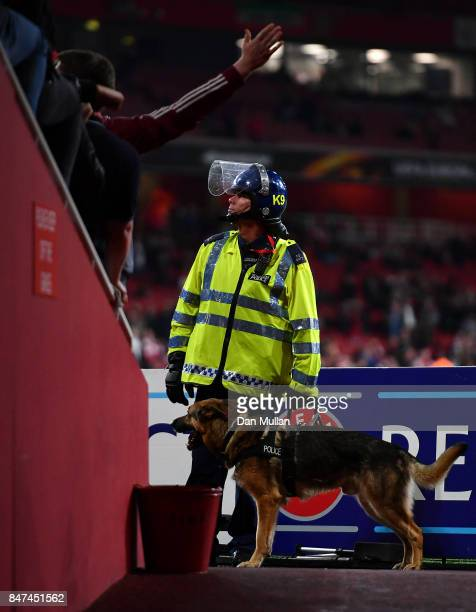 A police officer in riot stands with a police dog in front of the FC Koeln fans prior to the UEFA Europa League group H match between Arsenal FC and...