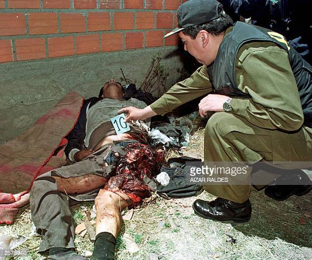 A police officer inspects 09 October 2003 the corpse of miner Luis Atahuchi hit by the blast of a dinamite stick during clashes between protesters...