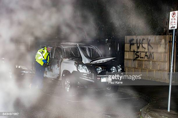 A police officer inspects a burnedout Toyota 4WD vehicle on Tonbridge Way after a suspected fire bombing outside the Thornllie Australian Islamic...