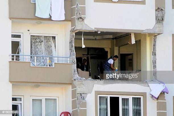 A police officer inspects a damaged apartment at the explosion site on October 16 2016 near the Syrian border in Gaziantep after a bomber blew...