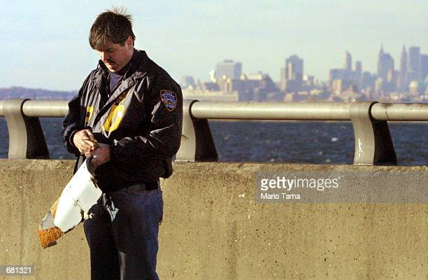 A police officer inspects an apparent piece of plane wreckage near the crash site after American Airlines flight 587 carrying 255 people crashed...