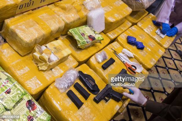A police officer inspects seized drugs and guns during a press conference in Bangkok on May 11 2018 Ten million madeinMyanmar 'yaba' pills and nearly...