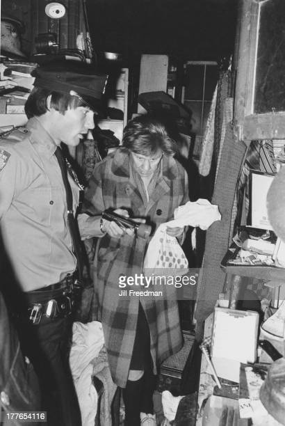A police officer inspects the cramped living conditions of an elderly resident in a tenement apartment Lower East Side New York City circa 1970