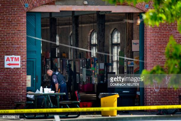 A police officer inspects the crime scene at the Roebling Market on June 17 the morning after a shooting at an allnight art festival injured 20...