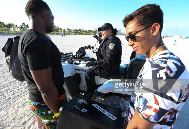 A police officer instructs students of Florida State University to lower the volume on their portable speaker system as they leave the beach during...