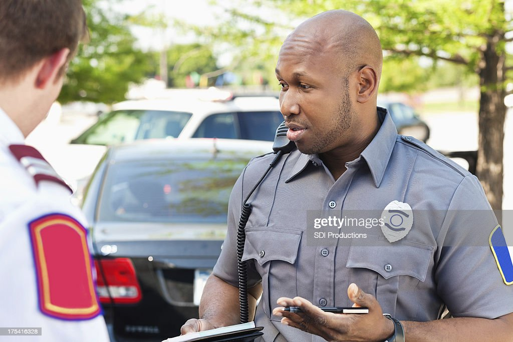Police officer interogating people at an emergency scene : Stock Photo