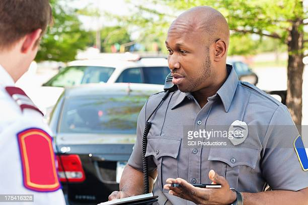 police officer interogating people at an emergency scene - law enforcement stock photos and pictures