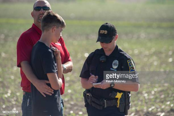 A police officer interviews a student and adult outside Noblesville West Middle School after a shooting at the school on May 25 2018 in Noblesville...