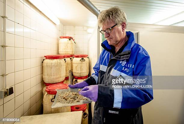 A police officer investigates a drugslab where MDMA was produced in Eindhoven in the south of The Netherlands on April 4 2016 Hundreds of police...