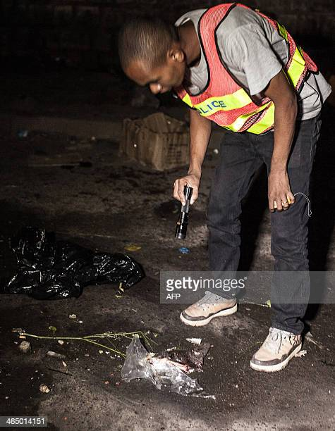 A police officer investigates at the site of a grenade explosion in Antananarivo's Anosy district on January 25 just hours after the island's newly...