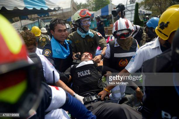 Police officer is carried to an ambulance after he was shot in the head by sniper fire during a police operation to reclaim the protest site at Phan...